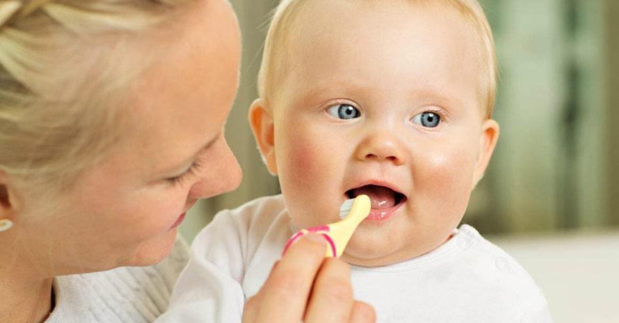 mom brushing her child's teeth