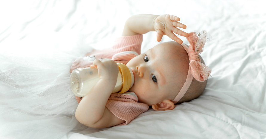 baby girl lying in the bed and holding a baby bottle