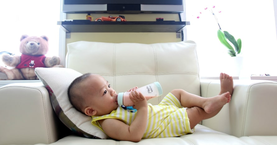 baby drinking milk and lying on the white sofa