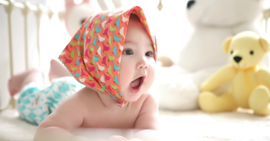 baby lies in a scarf